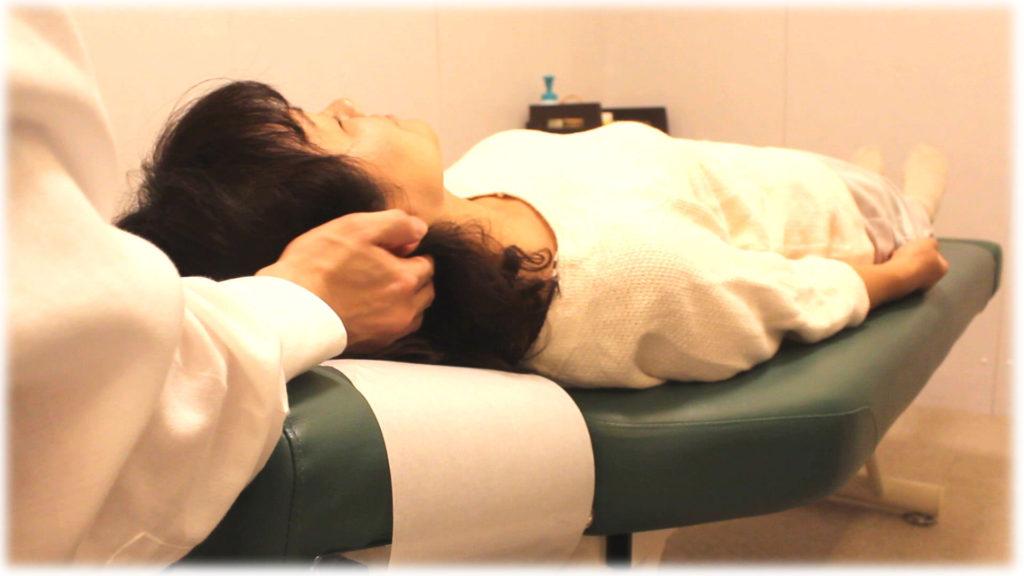 仰向けで頚の整体施術をしている写真