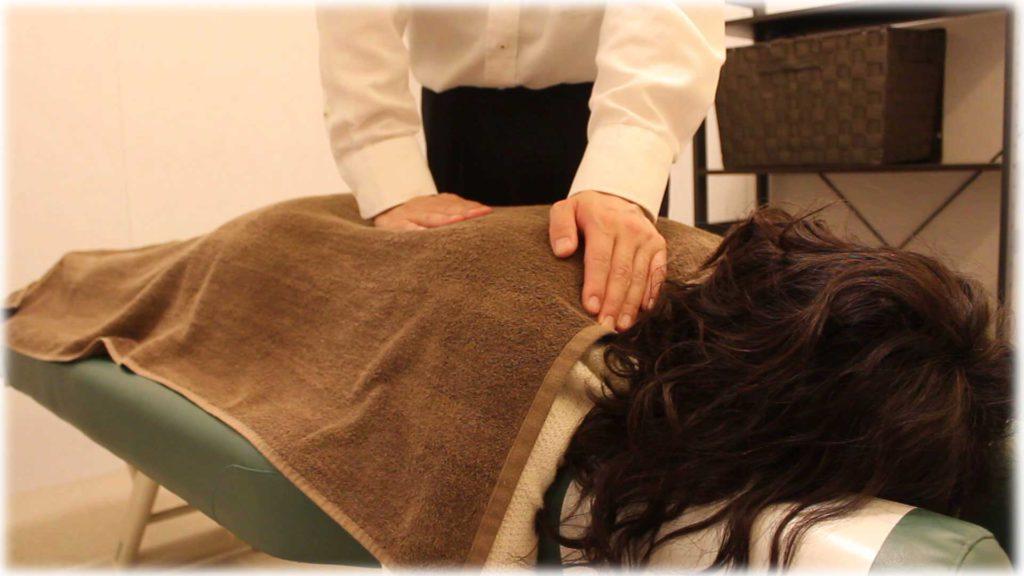 うつ伏せで背中を治療している写真
