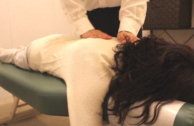うつ伏せで背中を施術している写真1
